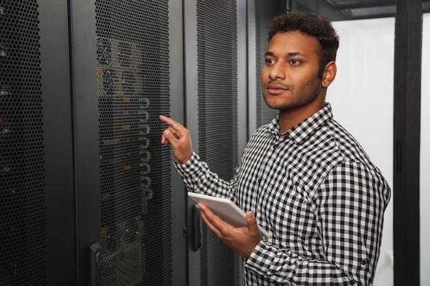 Sguardo più da vicino. ragazzo informatico attraente che ispeziona l'armadio del server e utilizza il tablet