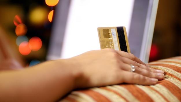 Primo piano 4k filmati della mano femminile che tiene credito mentre si effettuano ordini nell'e-store per natale e capodanno. colpo di concetto di shopping online ed e-commerce.