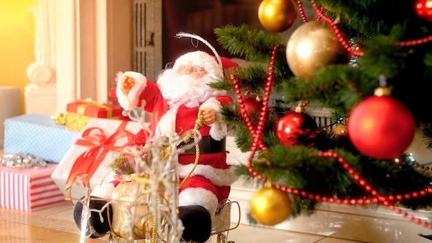 Primo piano 4k riprese della bambola di babbo natale sotto l'albero di natale decorato accanto al camino in soggiorno. scatto perfetto per feste e feste invernali