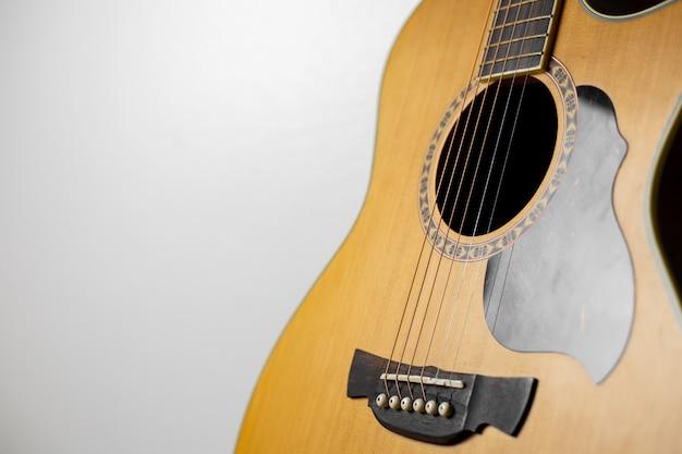 Chitarra acustica del primo piano su bianco