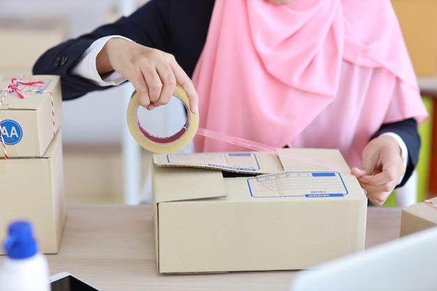Mani della donna musulmana asiatica attiva del primo piano in vestito blu che si siede e che lavora in linea
