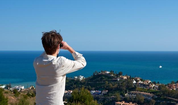Un primo piano di un giovane esploratore avventuroso che guarda attraverso il binocolo la città in riva al mare