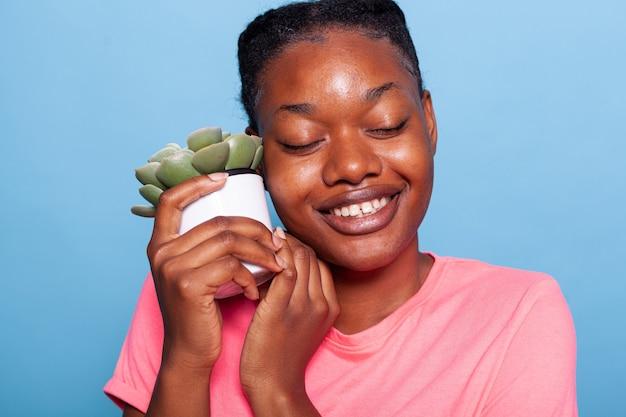 Primo piano di una giovane donna afroamericana che si gode l'hobby del giardinaggio