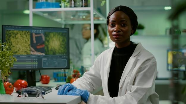 Primo piano della donna biologa africana che esamina la macchina fotografica mentre lavora nel laboratorio di agronomia biologica. team di specialisti alla ricerca di mutazioni genetiche che sviluppano test medico-scientifici del dna ogm
