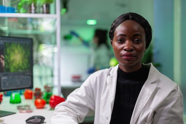 Primo piano della donna del biologo africano che esamina la macchina fotografica?