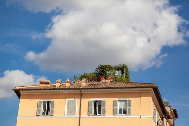 Primo piano del tetto della costruzione antica con cielo blu e nuvole bianche nella città di roma, italia