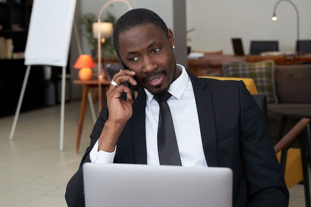 Primo piano di giovane uomo africano arrabbiato che grida mentre parlando sullo smartphone