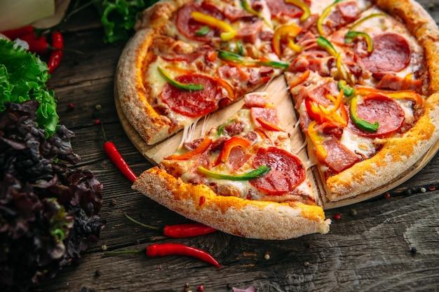 Primo piano su peperoni caldi appetitosi della pizza con salame