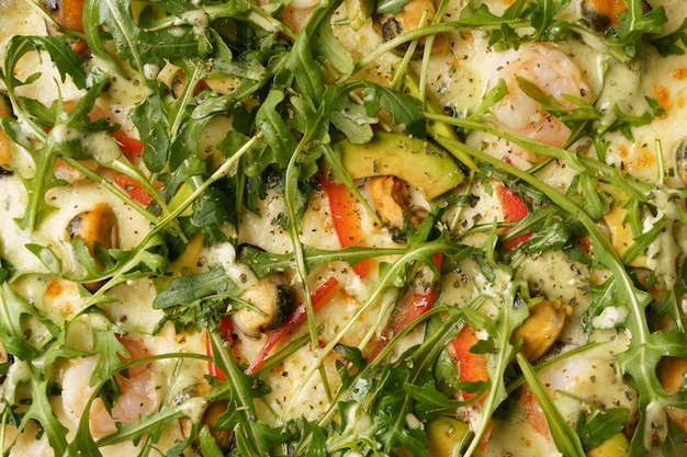 Primo piano della pizza italiana aromatica con rucola del pepe rosso della mozzarella di avocado dei gamberetti delle cozze