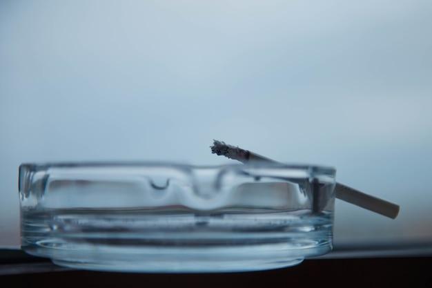 Primo piano di un posacenere con il fumo di sigaretta su bluegray neutro