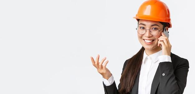 Il primo piano della donna d'affari asiatica gestisce l'ingegnere aziendale in casco di sicurezza e tuta con telefono con...