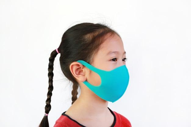 L'usura asiatica del bambino del primo piano protegge la maschera su bianco
