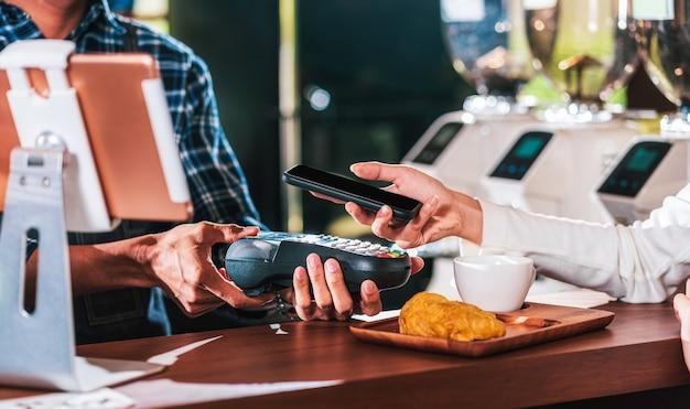 Primo piano della mano dell'uomo del cliente asiatico che paga denaro tramite il canale senza contatto tramite l'applicazione di mobile banking