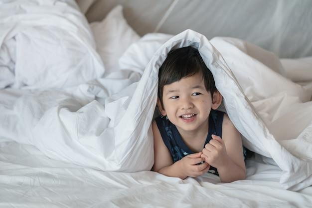 Bambino asiatico del primo piano sul letto sotto la coperta con il fronte di sorriso di mattina