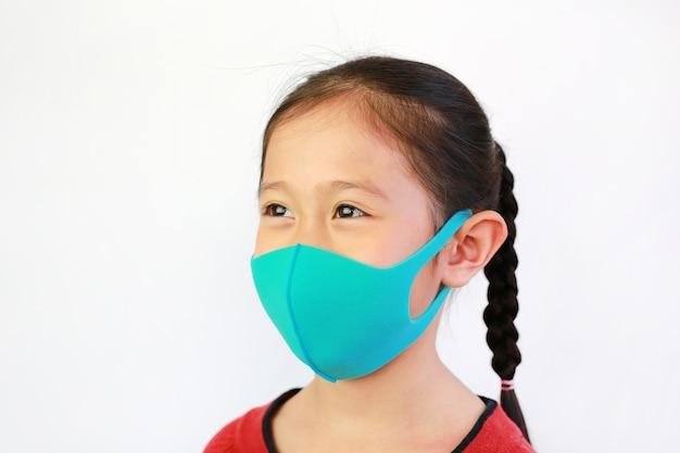 Maschera di protezione asiatica di usura della bambina del primo piano isolata