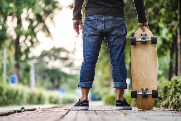 Uomo asiatico del primo piano che tiene surfskate o skateboard nel parco all'aperto