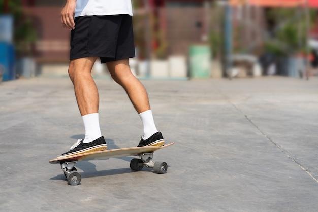 Gamba dell'uomo asiatico del primo piano che gioca sul surfskate all'aperto