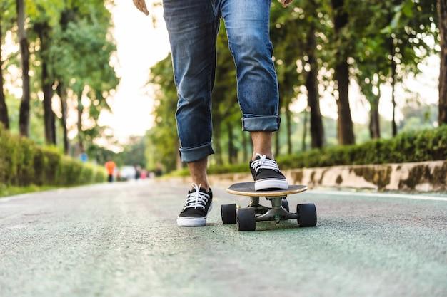 Primo piano gamba uomo asiatico su surfskate o skateboard nel parco all'aperto
