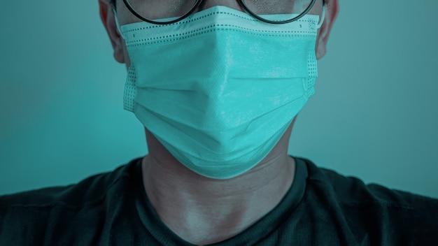 Primo piano dell'uomo asiatico che indossa una maschera contro il coronavirus o il covid19