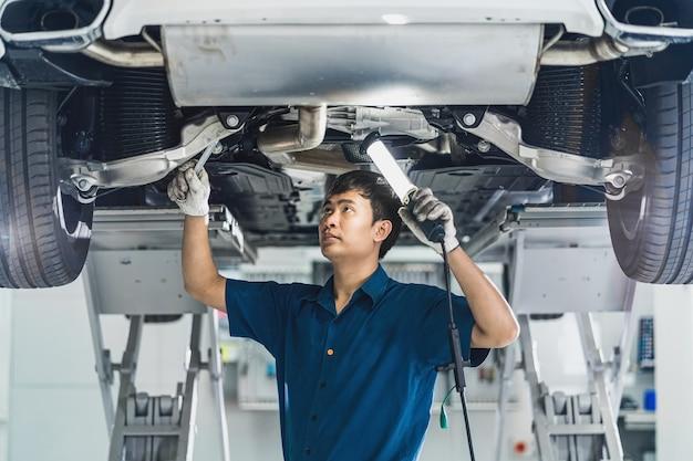 Primo piano meccanico asiatico che ripara a mano sotto l'auto nel centro servizi di manutenzione