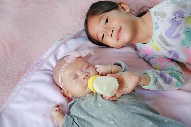 Sorella asiatica del primo piano che alimenta la neonata con la bottiglia per il latte sul letto di menzogne
