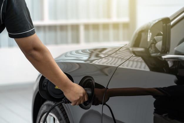 La mano asiatica del tecnico del primo piano sta caricando l'automobile elettrica o ev nel centro servizi per manutenzione