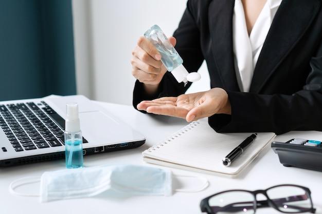 Primo piano della mano della donna asiatica utilizzando gel igienizzante per disinfettare le mani alla scrivania in ufficio