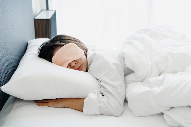 Primo piano della donna asiatica nella maschera di sonno che si trova nel comodo letto bianco al mattino