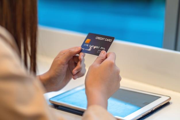 Donna asiatica del primo piano che utilizza la carta di credito con la compressa per lo shopping online nel grande magazzino sopra la parete del negozio di abbigliamento, portafoglio di soldi di tecnologia e concetto di pagamento online, modello di carta di credito