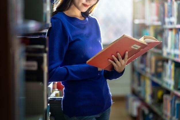 Primo piano giovane studente asiatico in abito casual in piedi e mano che tiene il libro e legge