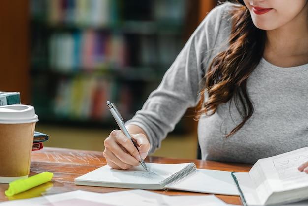 Primo piano di un giovane studente asiatico che scrive a mano i compiti nella biblioteca dell'università o del college con vari
