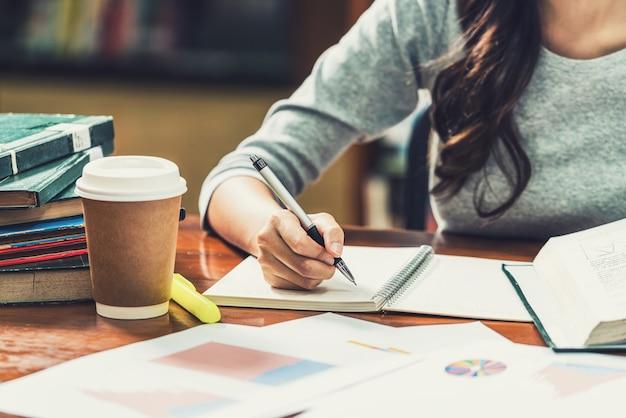 Primo piano del giovane studente asiatico che scrive a mano i compiti nella biblioteca dell'università o del collega