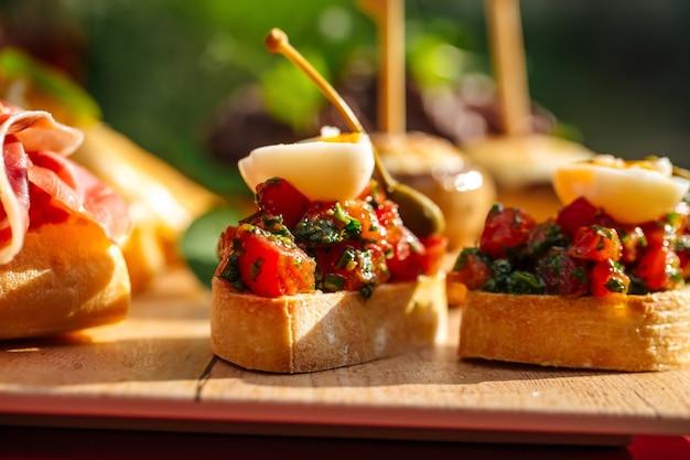 Primo piano sulle tapas spagnole assortite con diversi condimenti sulla tavola di legno