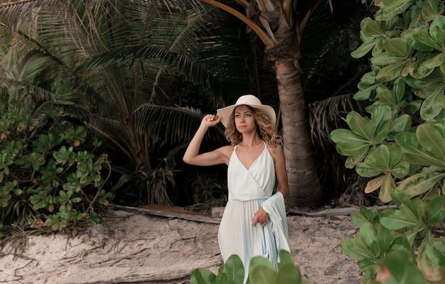 Donna adulta caucasica attraente e bella del primo piano che sorride sulla spiaggia sabbiosa tropicale.