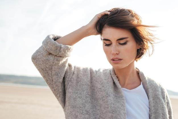 Primo piano della giovane donna pensierosa attraente in cappotto sulla spiaggia in autunno