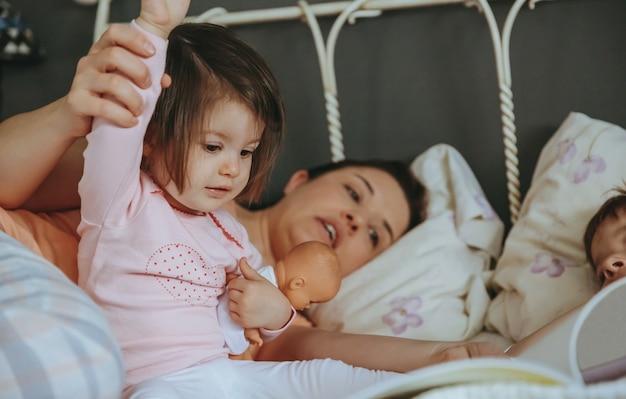 Primo piano della figlia del bambino che legge il libro di storia con sua madre e suo fratello nel letto. concetto di tempo libero per la famiglia nel fine settimana.