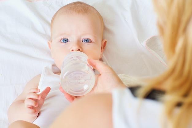 Primo piano del bambino che mangia cibo bottiglia d'acqua mamma nutre la protezione dei bambini dei pasti dei bambini