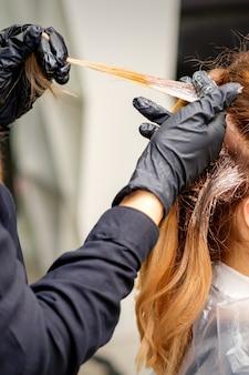 Primo piano vista posteriore delle mani dei parrucchieri nei guanti che applicano la tintura a una ciocca di capelli di una giovane donna dai capelli rossi in un parrucchiere