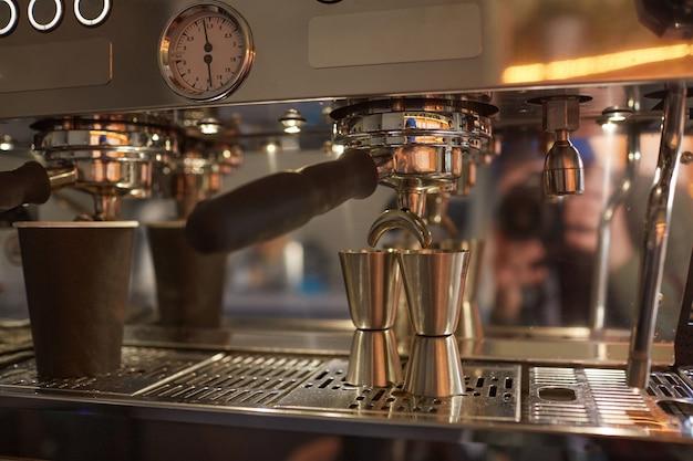 Primo piano immagine di sfondo della macchina da caffè industriale che produce caffè espresso in un bar o in una caffetteria, spazio di copia