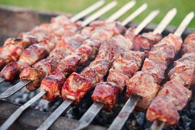 Primo piano del barbecue alla griglia kebab su spiedini che cucinano all'aperto