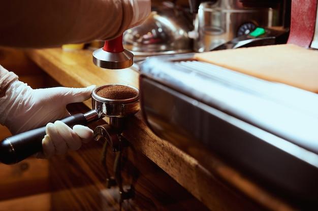 Primo piano del barista che tiene il titolare del caffè con caffè macinato vicino alla macchina da caffè professionale.