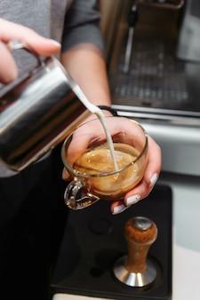 Primo piano del barista che versa il latte nell'arte cappuccino o latte.