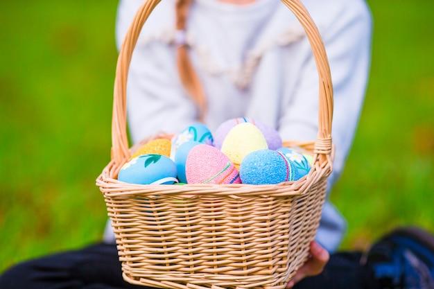 Canestro del primo piano in pieno delle uova di pasqua variopinte in mani dei bambini