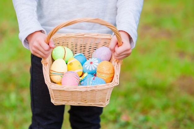 Canestro del primo piano con le uova di pasqua variopinte in mani dei bambini