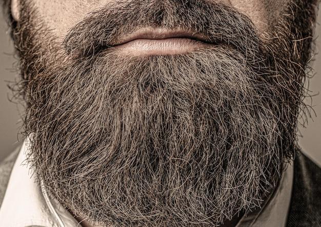 Primo piano di uomo barbuto maschio con baffi che crescono barba perfetta primo piano di giovane uomo barbuto