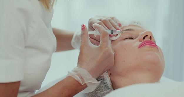 Primo piano delle mani dell'estetista che fanno l'iniezione di sollevamento della pelle del viso sul viso della giovane donna. bella paziente femminile che riceve procedura di bellezza. trattamento cosmetico.