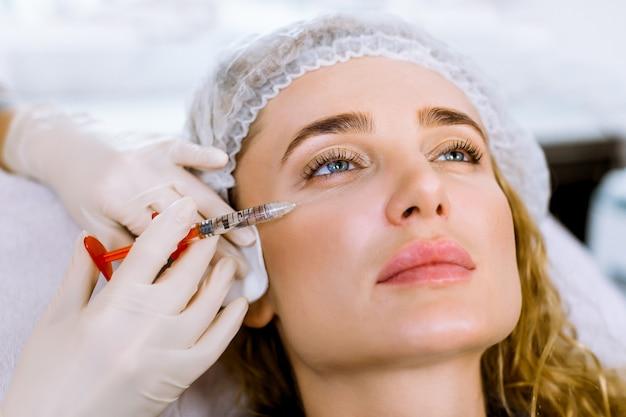 Primo piano delle mani dell'estetista in guanti che fanno iniezione di sollevamento della pelle facciale al fronte della donna. bella giovane donna in cappuccio sterile medico che riceve la procedura di bellezza nella moderna clinica di cosmetologia
