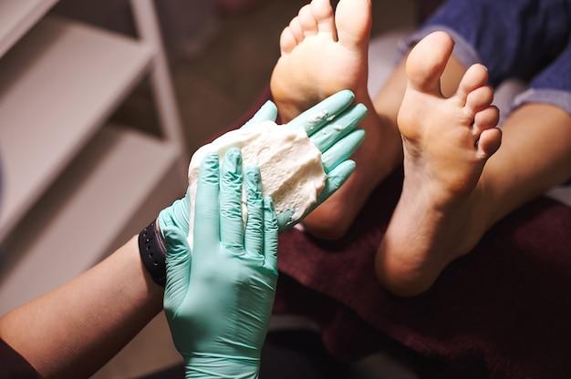Primo piano delle mani e dei piedi della donna dell'estetista che ha una pedicure in un centro termale di bellezza. concetto di cura del corpo