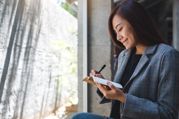 Primo piano di una bella imprenditrice asiatiche in possesso e la scrittura su un notebook