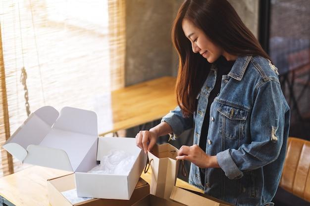 Primo piano di bella donna asiatica che si apre e che guarda il sacchetto della spesa interno a casa per la consegna e il concetto online di acquisto